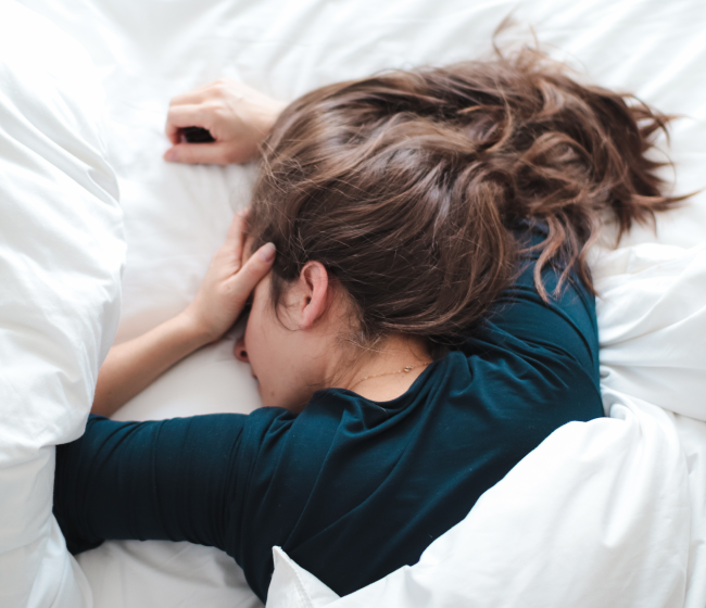 woman in blue shirt laying in bed covering her head with her hand